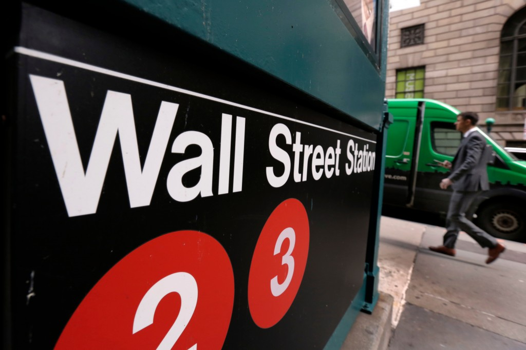 FILE- In this April 5, 2018, file photo, a sign for a Wall Street subway station is shown in New York. Stocks are opening lower on Wall Street, Thursd