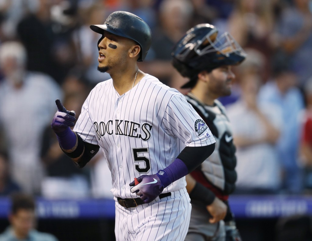 Colorado Rockies' Carlos Gonzalez gestures as he crosses home plate after hitting a solo home run off Arizona Diamondbacks relief pitcher Jorge De La