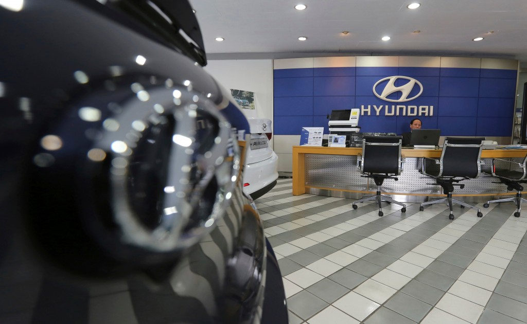 FILE - In this Jan. 25, 2018 file photo, an employee of Hyundai Motor Co. waits for customers at the company's showroom in Seoul, South Korea. Hyundai