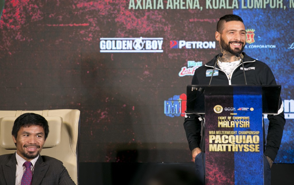 Argentine WBA welterweight champion Lucas Matthysse speaks as Philippine senator and boxing hero Manny Pacquiao smiles during a press conference in Ku