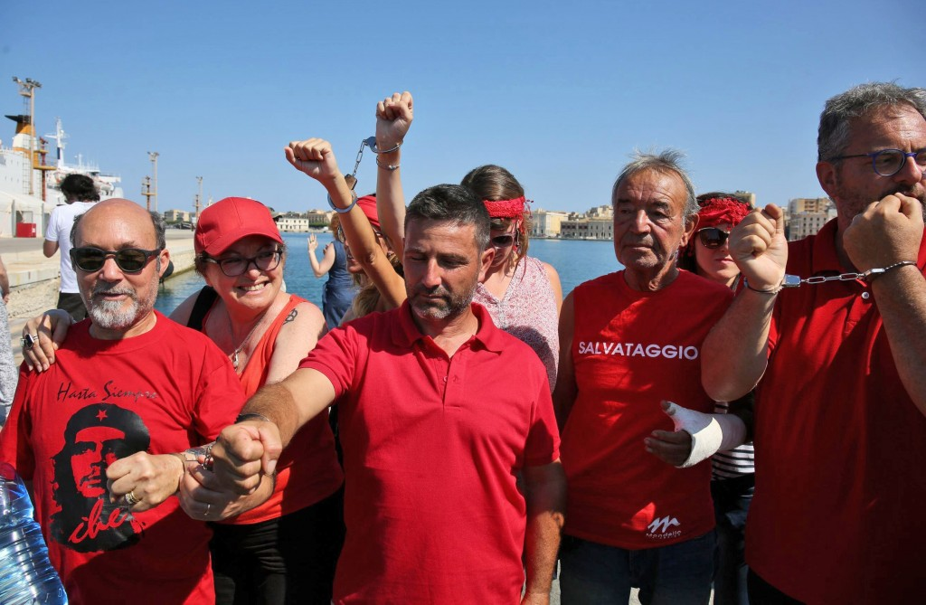 Activists wearing red T-sirts that symbolize a broader welcome to migrants, demonstrate by handcuffing their arms as they wait for the Italian Coast G