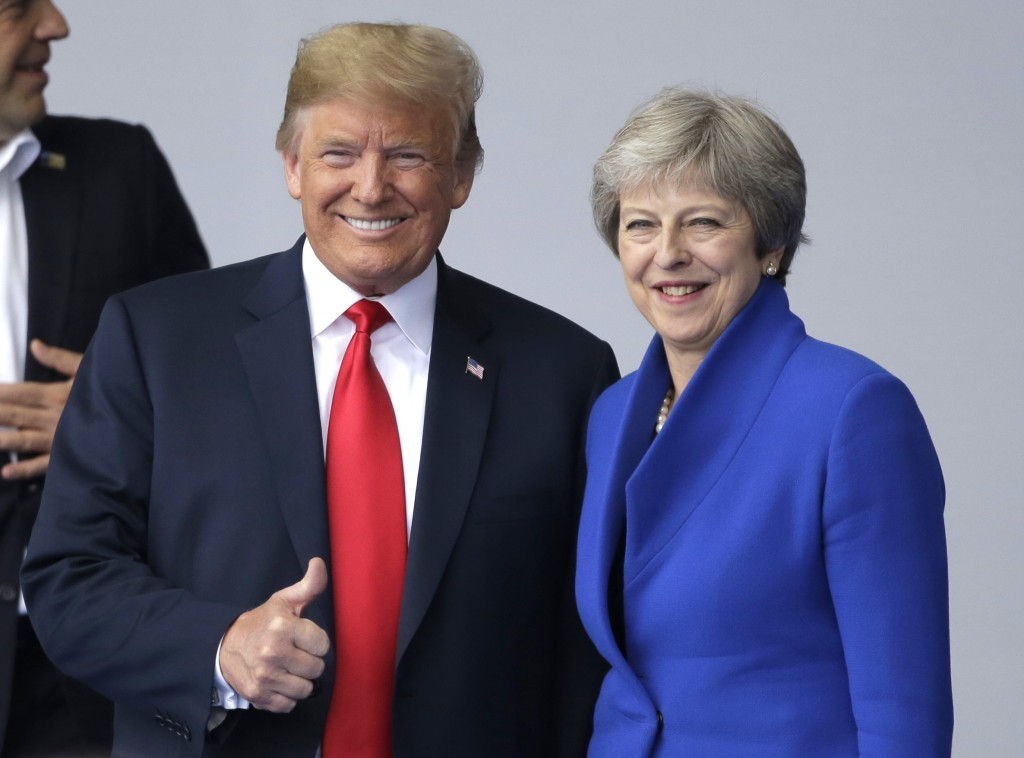 In this July 11, 2018, photo, U.S. President Donald Trump, left, talks to British Prime Minister Theresa May during a summit of heads of state and gov...