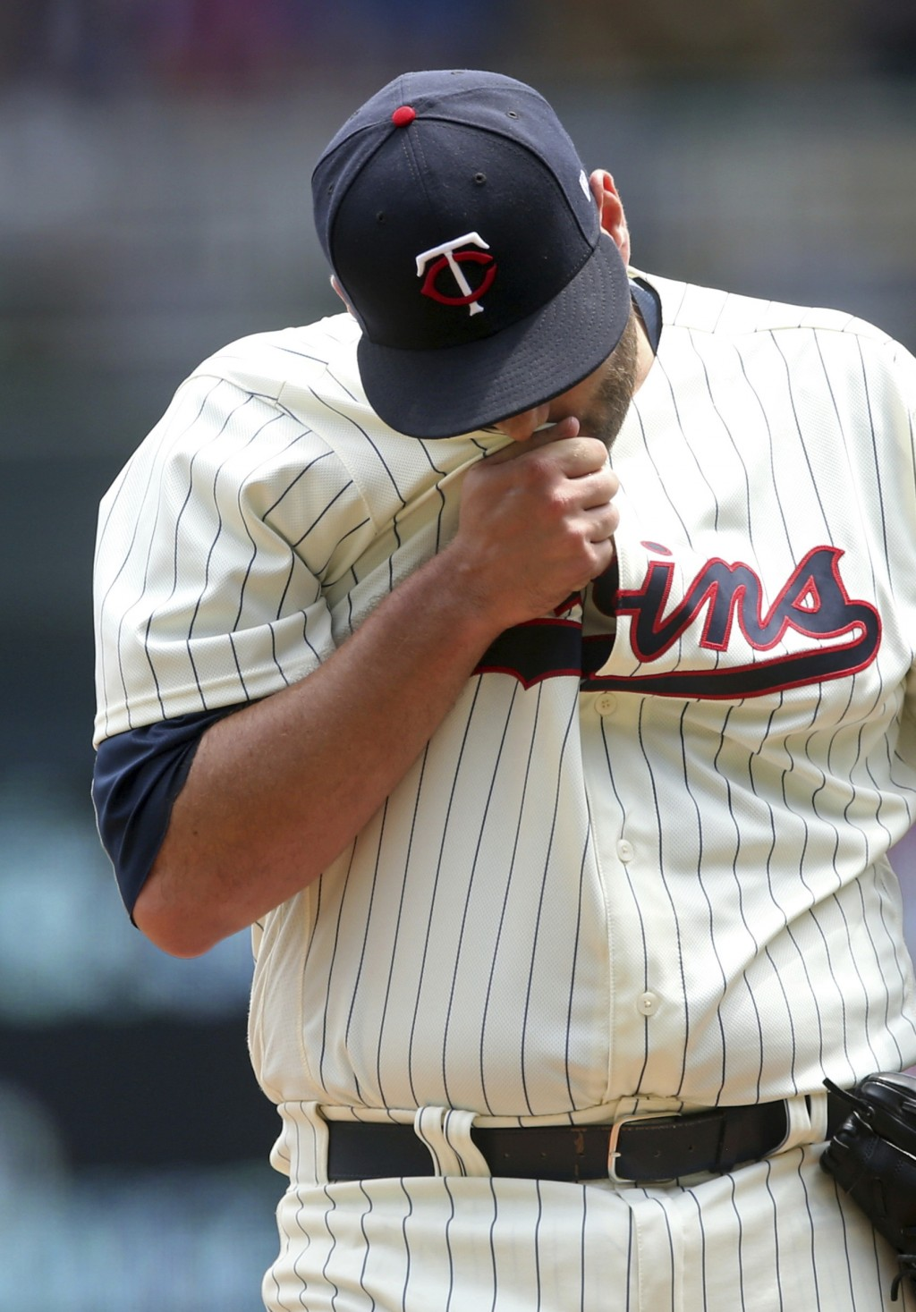 Minnesota Twins pitcher Lance Lynn wipes his face after giving up a solo home run to Kansas City Royals' Mike Moustakas in the third inning of a baseb