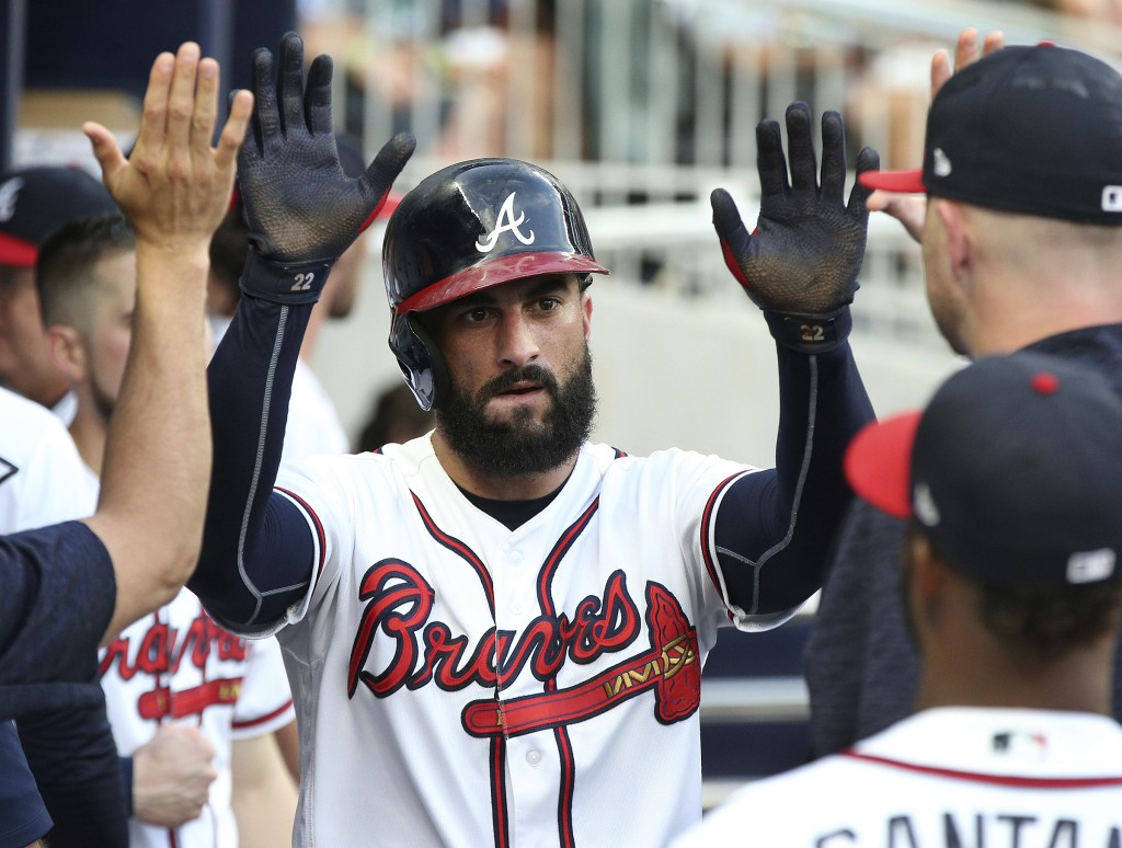 Atlanta Braves' Nick Markakis is congratulated after scoring against the Toronto Blue Jays during the second inning of a baseball game Wednesday, July