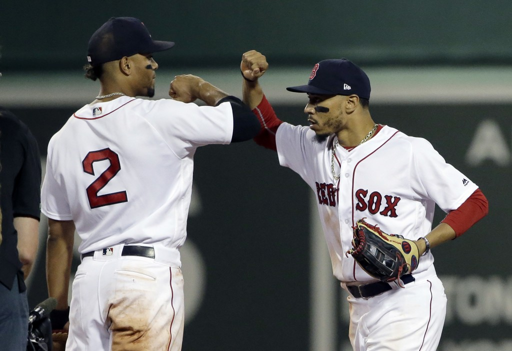 Boston Red Sox's Xander Bogaerts (2) and Mookie Betts, right, celebrate after the Red Sox defeated the Texas Rangers 4-2 in a baseball game Wednesday,