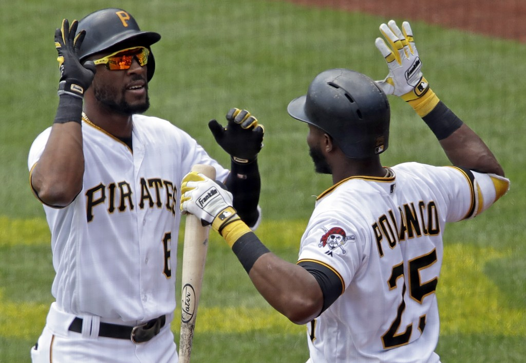 Pittsburgh Pirates' Starling Marte, left, is greeted by Gregory Polanco (25) as he returns to the dugout after hitting a two-run home run off Washingt