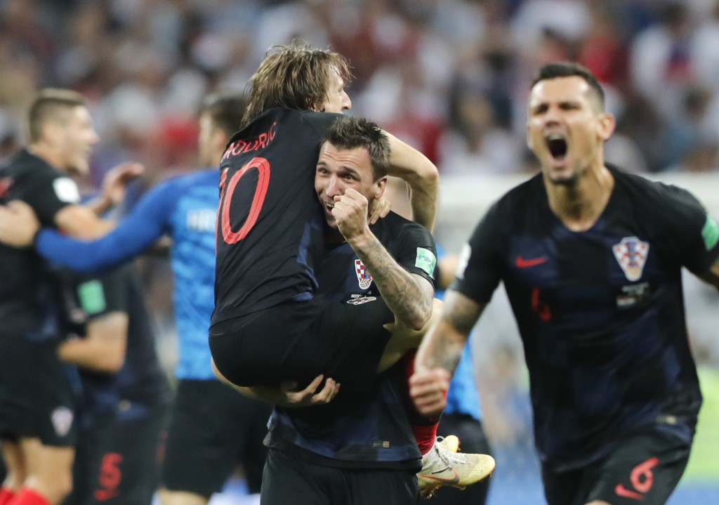 Croatia's Mario Mandzukic, center, carries Luka Modric when celebrating after his team advanced to the final during the semifinal match between Croati