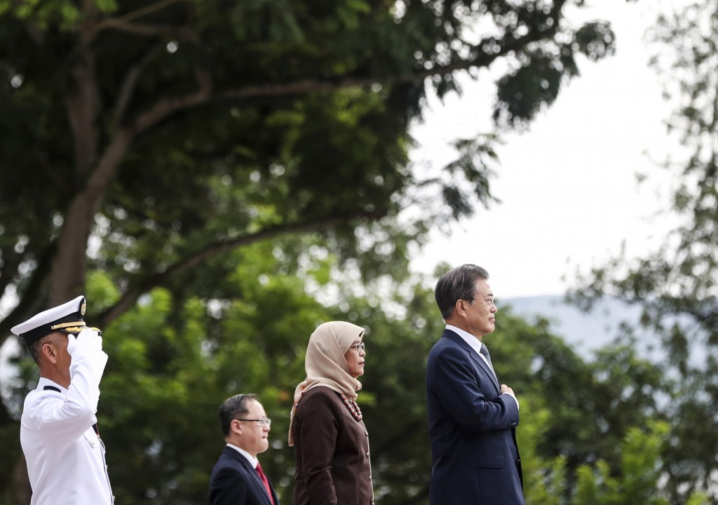 South Korea's President Moon Jae-in, right, stands with Singapore's President Halimah Yacob, second from right, while listening their national anthems