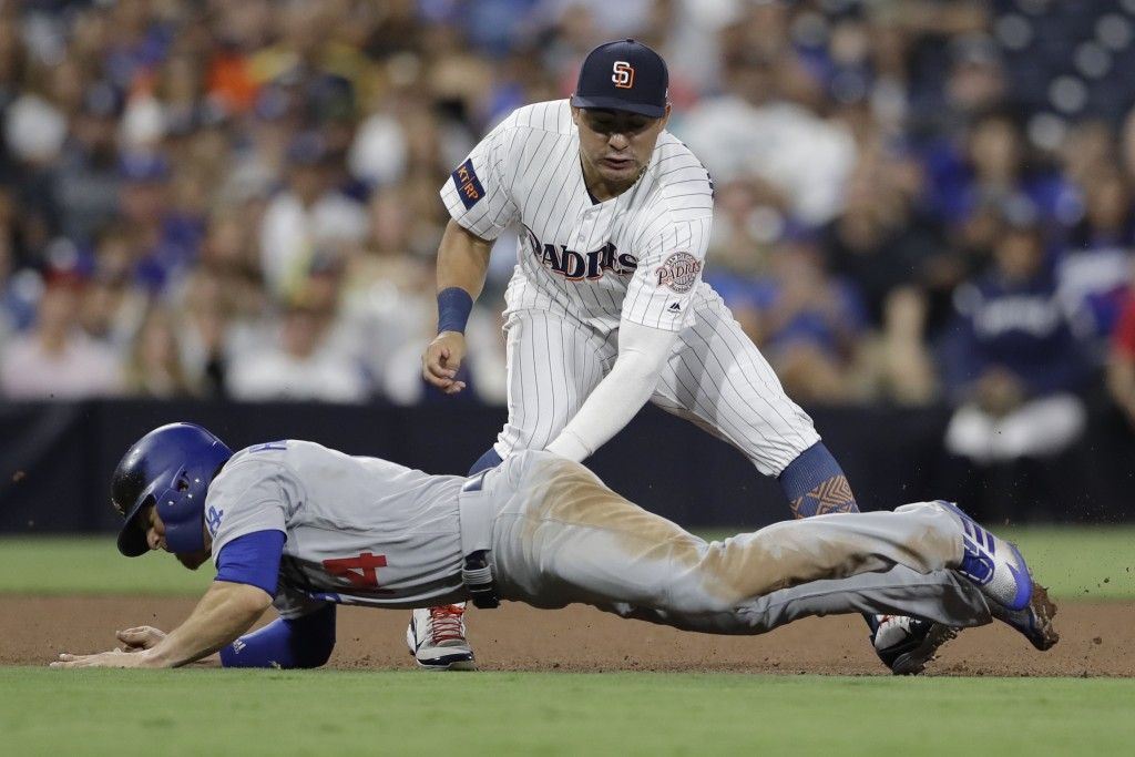 San Diego Padres third baseman Christian Villanueva, above, tags out Los Angeles Dodgers' Enrique Hernandez before throwing to first for the out on Ma