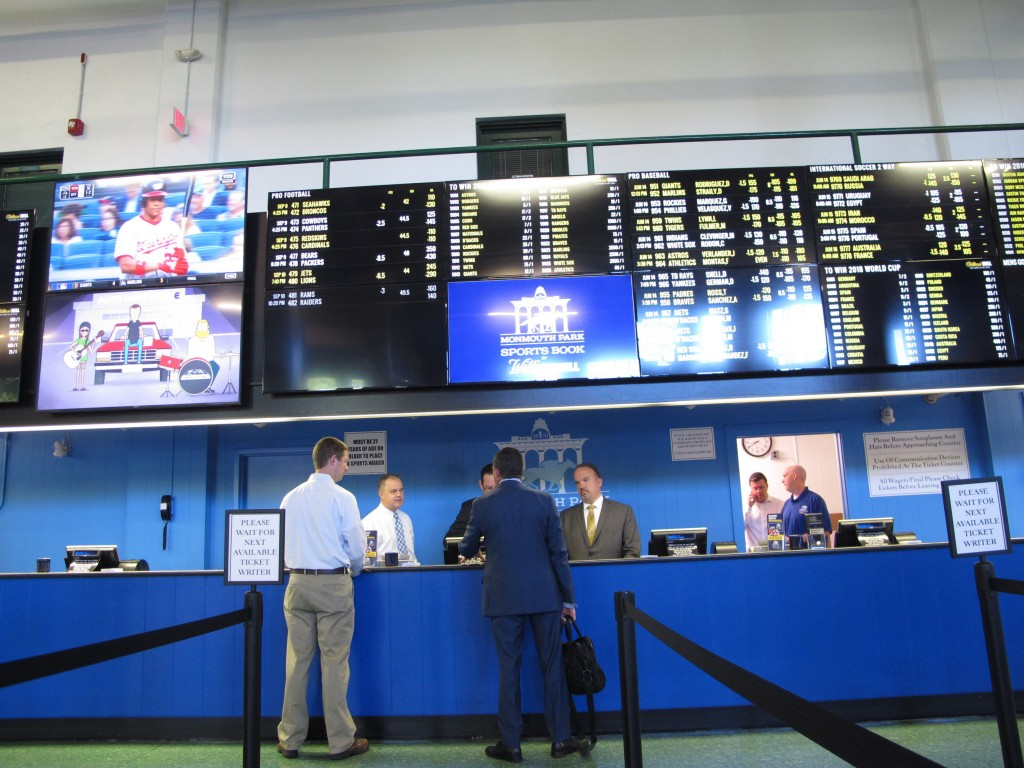 This June 14, 2018 photo shows staff at Monmouth Park racetrack in Oceanport N.J. preparing to begin taking sports bets moments before it became legal