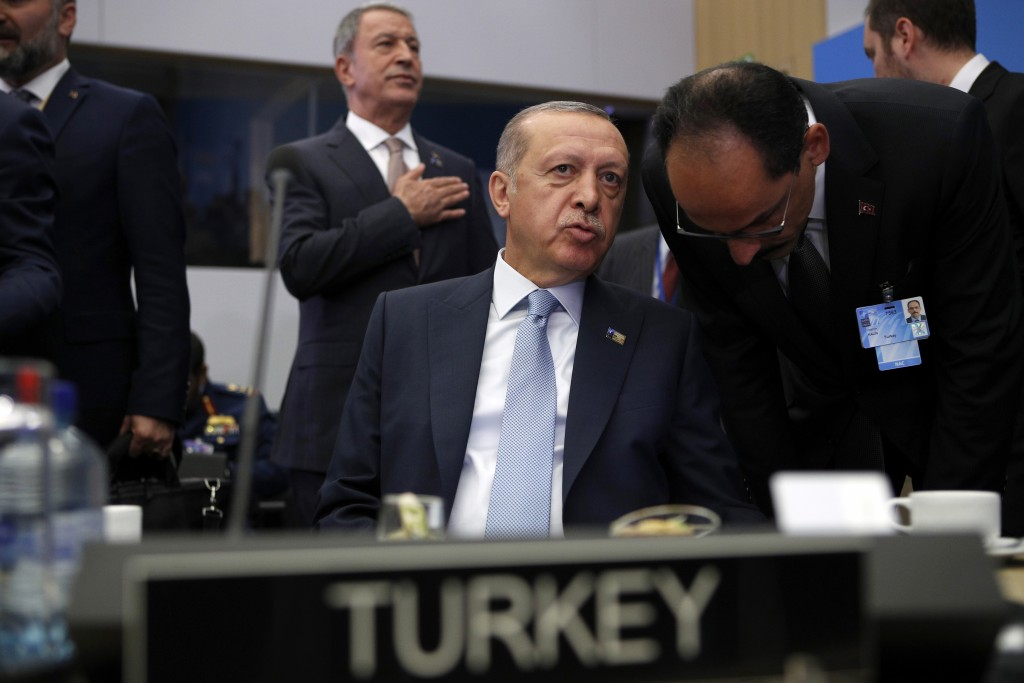 Turkish President Recep Tayyip Erdogan listens to his special adviser Ibrahim Kalin prior to a working session of a NATO summit of heads of state and