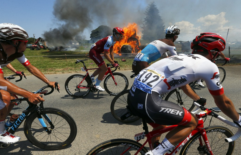 The pack rides past a burning haystack during the sixth stage of the Tour de France cycling race over 181 kilometers (112.5 miles) with start in Brest
