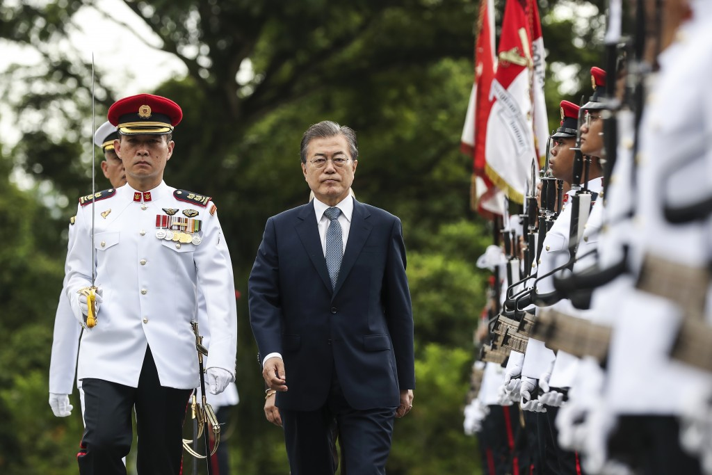 South Korea's President Moon Jae-in, second from left, reviews an honor guard during a welcome ceremony at the Istana or Presidential Palace in Singap