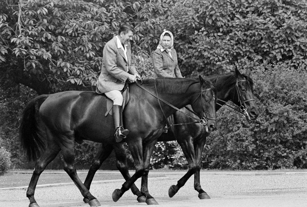 FILE - In this June 8, 1982 file photo, U.S. President Ronald Reagan, on Centennial, and Britain's Queen Elizabeth II, on Burmese, go horseback riding