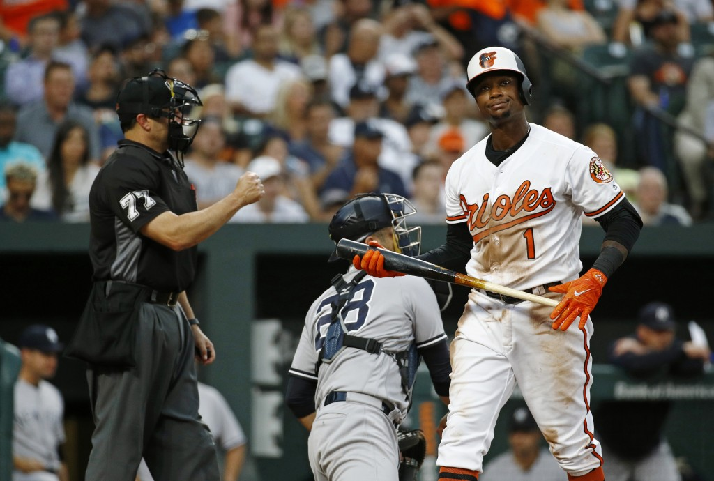 Baltimore Orioles' Tim Beckham, right, walks off the field past umpire Jim Reynolds and New York Yankees catcher Austin Romine after striking out swin