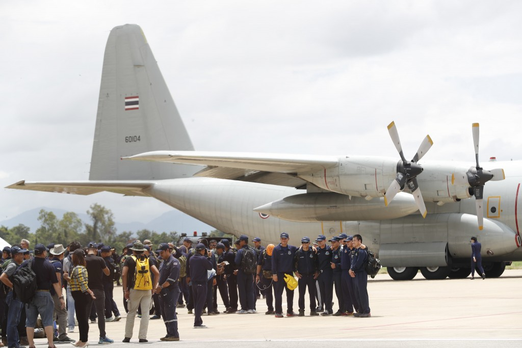 Thai Navy SEALs and military personnel take a group picture before they board a plane at the airport in Chiang Rai, northern Thailand, Thursday, July