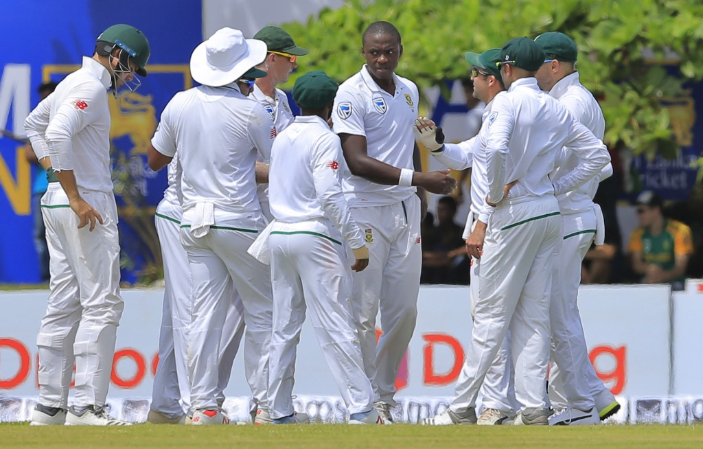 South African team members congratulate Kagiso Rabada, facing camera, for the dismissal of Sri Lanka's Danushka Gunathilaka during the first day's pla