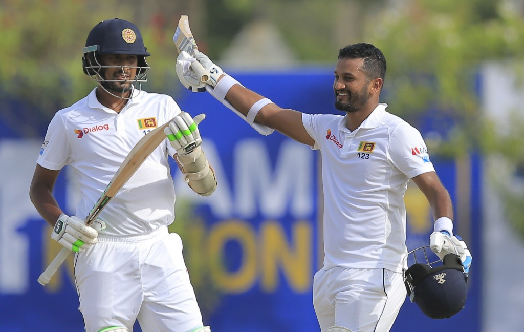Sri Lanka's Dimuth Karunaratne, right, celebrates scoring a century as Suranga Lakmal watches during the first day's play of their first test cricket