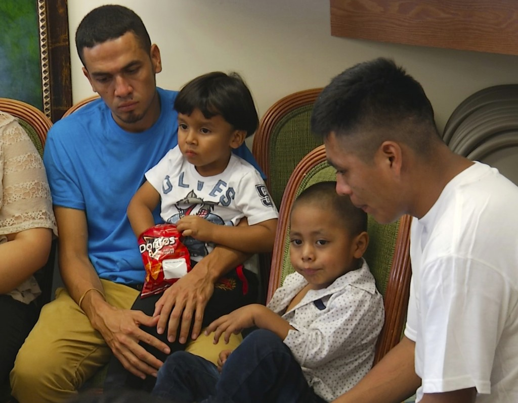 In this image taken from video, Javier Garrido Martinez, left and Alan Garcia, right, sit with their 4-year-sons at a news conference in New York, Wed