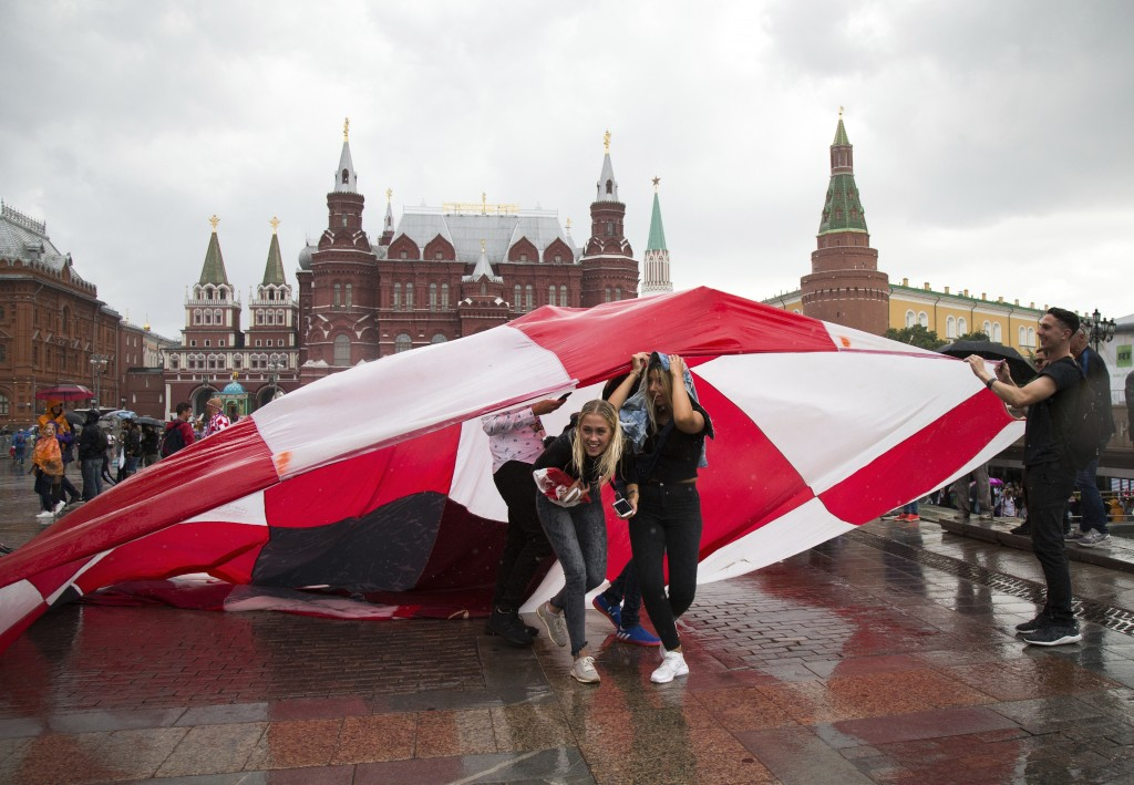 Soccer fans use a giant Croatian national flag as a shelter during the rain at Manezh Square near Red Square ahead of the semifinal soccer match betwe