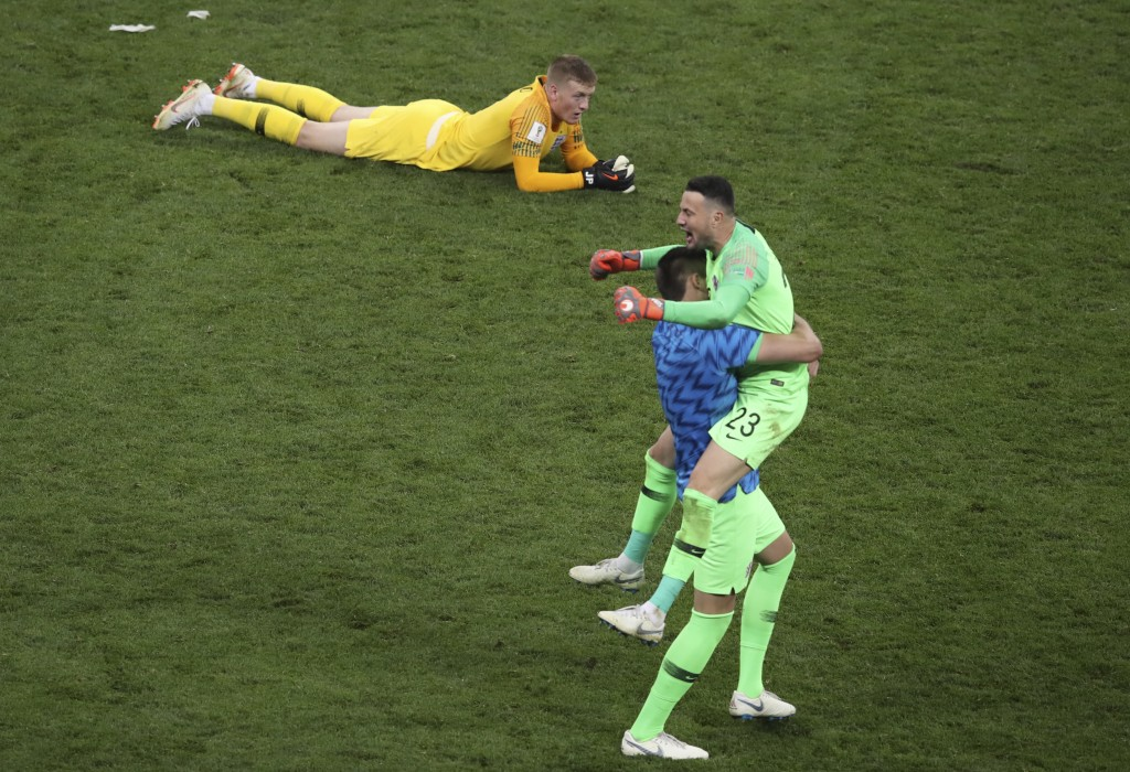 England goalkeeper Jordan Pickford lies down on the pitch as Croatia goalkeeper Danijel Subasic, right, celebrates at the end of the semifinal match b