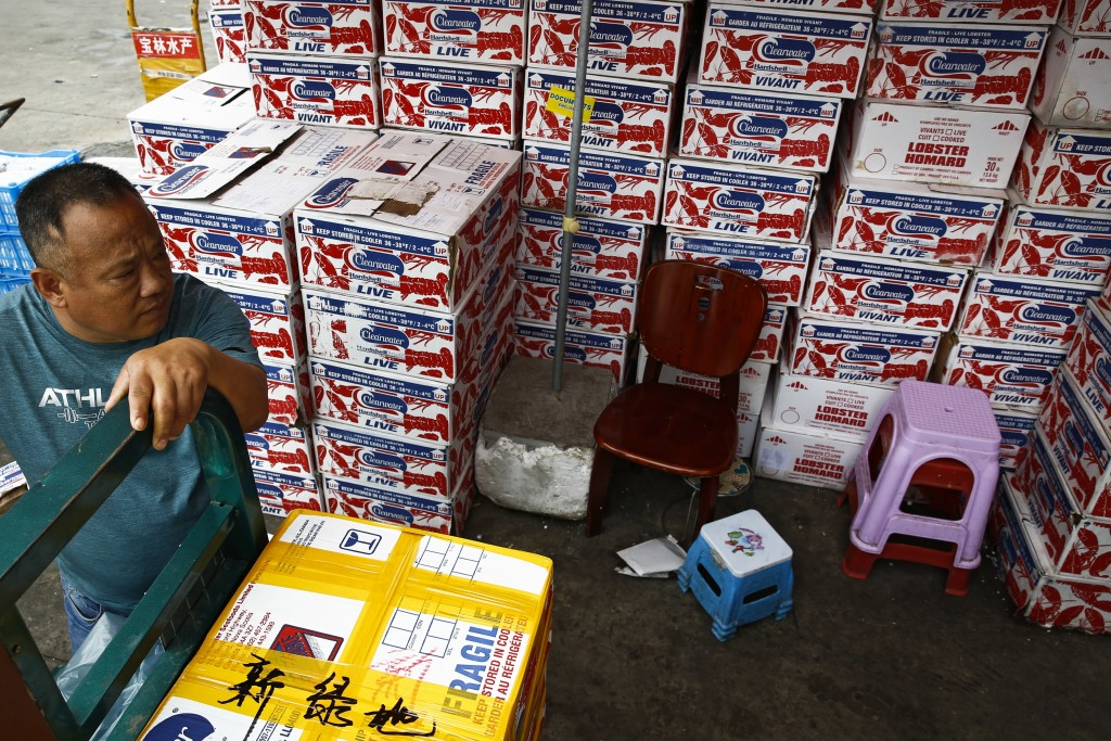 A man waits for the goods to be load on his tricycle at a dealer selling imported seafoods at the Jingshen seafood market in Beijing, Thursday, July 1