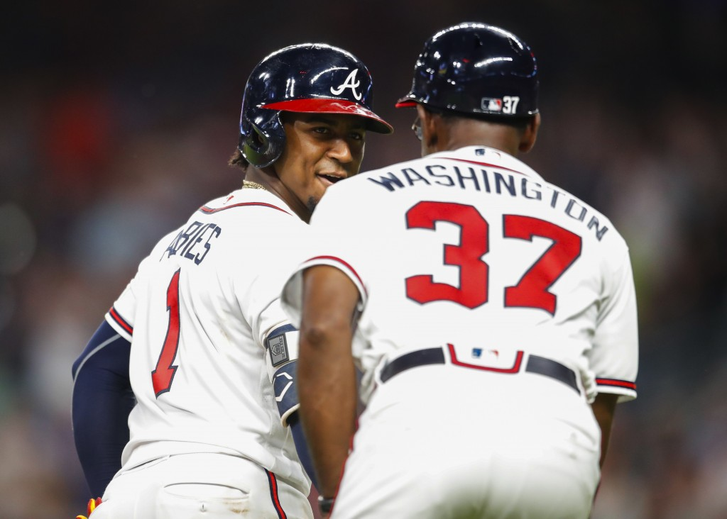 Atlanta Braves' Ozzie Albies (1) rounds third and shakes hands with third base coach Ron Washington (37) after hitting a solo home run during the sixt