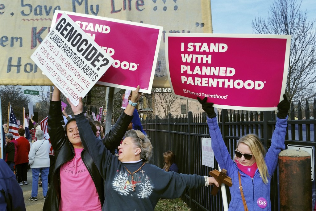 FILE - In this Feb. 11, 2017, file photo, a Planned Parenthood supporter and opponent try to block each other's signs during a protest and counter-pro