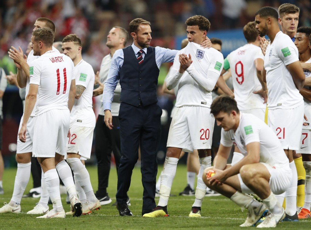 England head coach Gareth Southgate, center left, embraces England's Dele Alli at the end of the semifinal match between Croatia and England at the 20