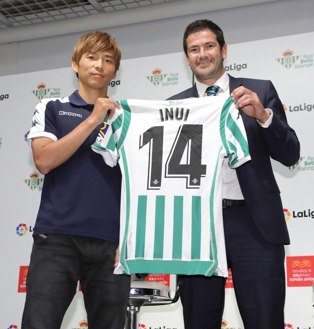 Japan's Takashi Inui, left, poses with his Real Betis' shirt as he received from the team's Business General Manager Ramon Alarcon, at the Spanish emb