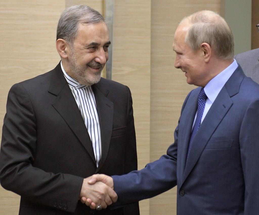 Russian President Vladimir Putin, right, shakes hands with Ali Akbar Velayati, a senior adviser to Iran's Supreme Leader Ayatollah Ali Khamenei, at No