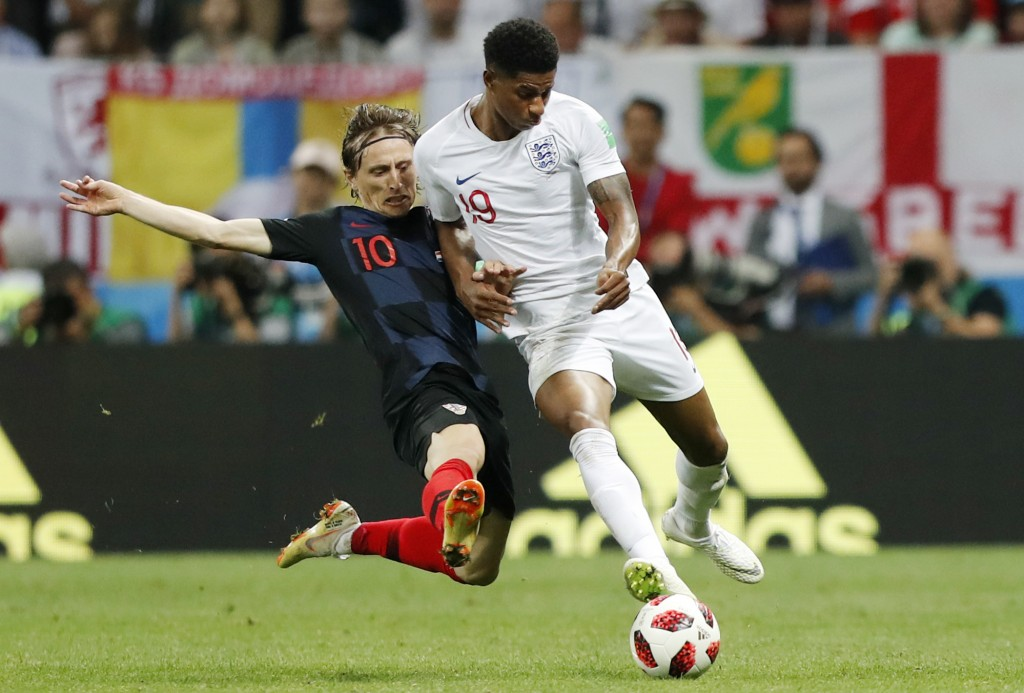 Croatia's Luka Modric, left, and England's Marcus Rashford challenge for the ball during the semifinal match between Croatia and England at the 2018 s