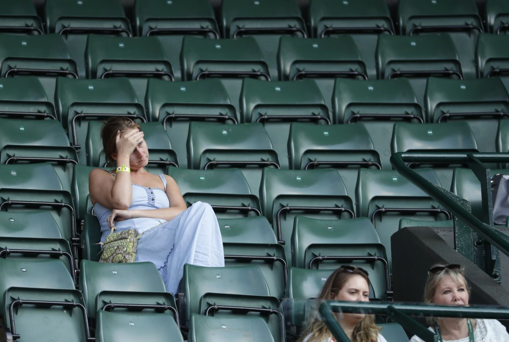 Spectators attend the men's singles quarterfinal tennis match between John Isner of the United States and Canada's Milos Raonic, at the Wimbledon Tenn