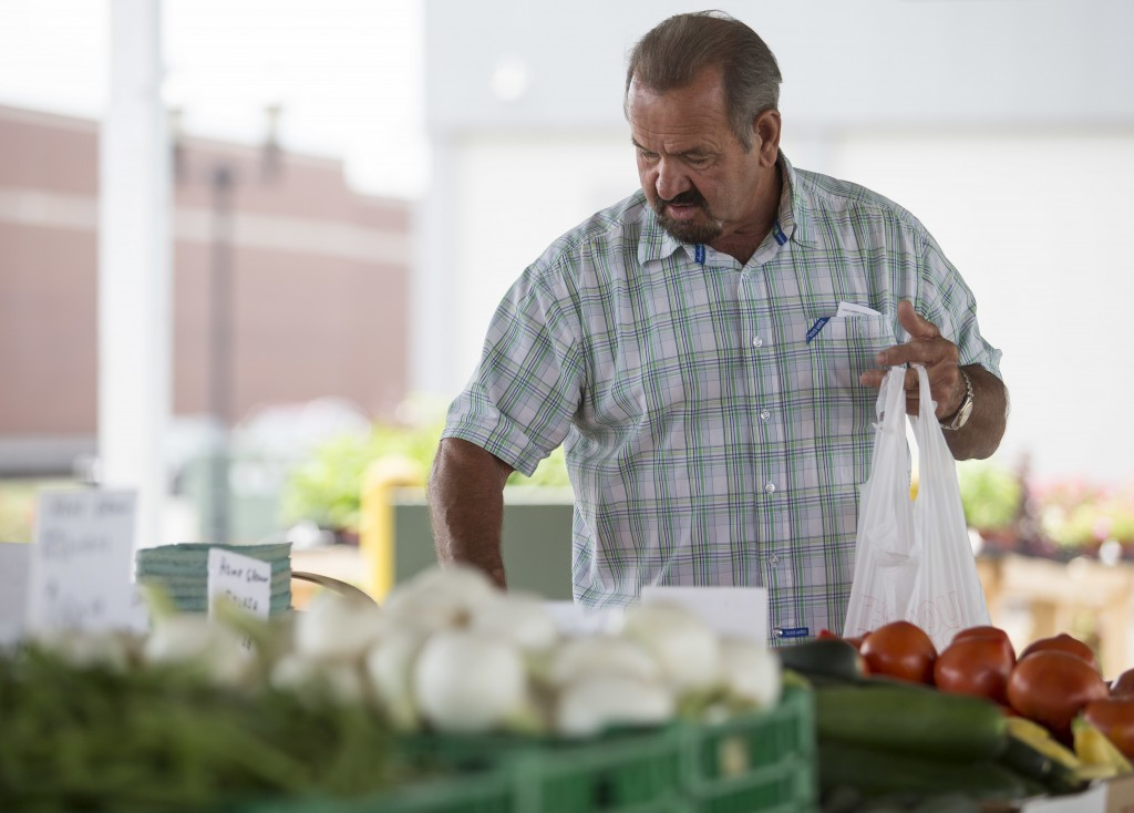 FILE- In this June 13, 2018, file photo, Bob Harris carefully selects which tomatoes to buy at Paducah, Kentucky's Downtown Farmers' Market. On Thursd