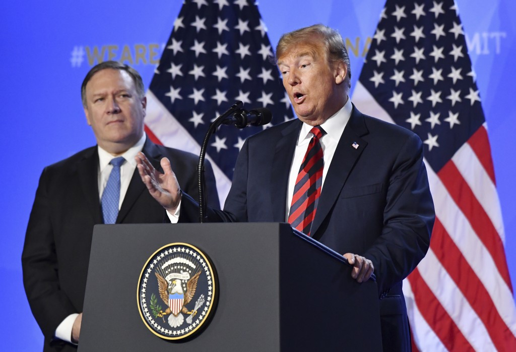 U.S. President Donald Trump is flanked by U.S. Secretary of State Mike Pompeo, left, as he speaks during a press conference after a summit of heads of