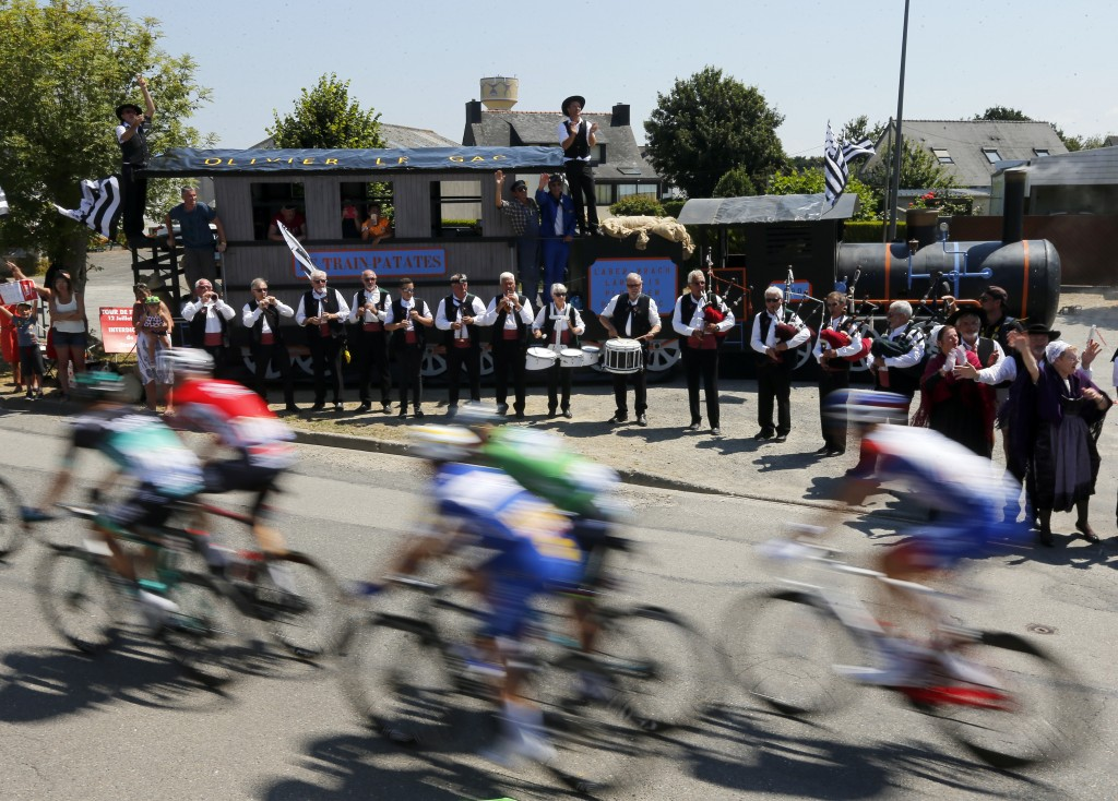 Musicians perform on the side of the road as the pack rides during the sixth stage of the Tour de France cycling race over 181 kilometers (112.5 miles
