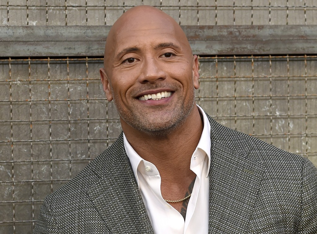 """FILE - In this April 4, 2018 file photo, Dwayne Johnson arrives at the world premiere of """"Rampage"""" at the Microsoft Theater in Los Angeles. Johnson, w"""