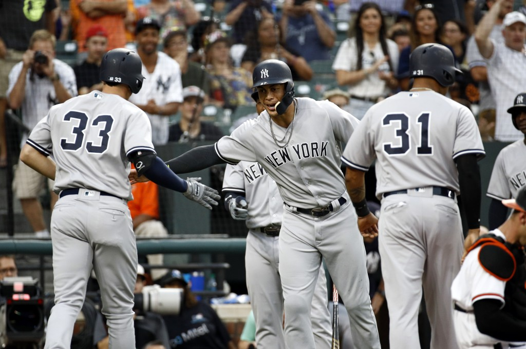 New York Yankees' Giancarlo Stanton, center, greets teammate Greg Bird after scoring on Bird's grand slam during the third inning against the Baltimor