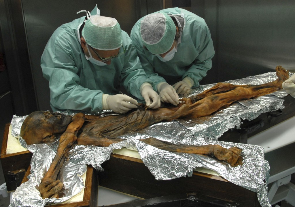 In this November 2010 photo provided by the South Tyrol Museum of Archaeology, researchers examine the body of a frozen hunter known as Oetzi the Icem