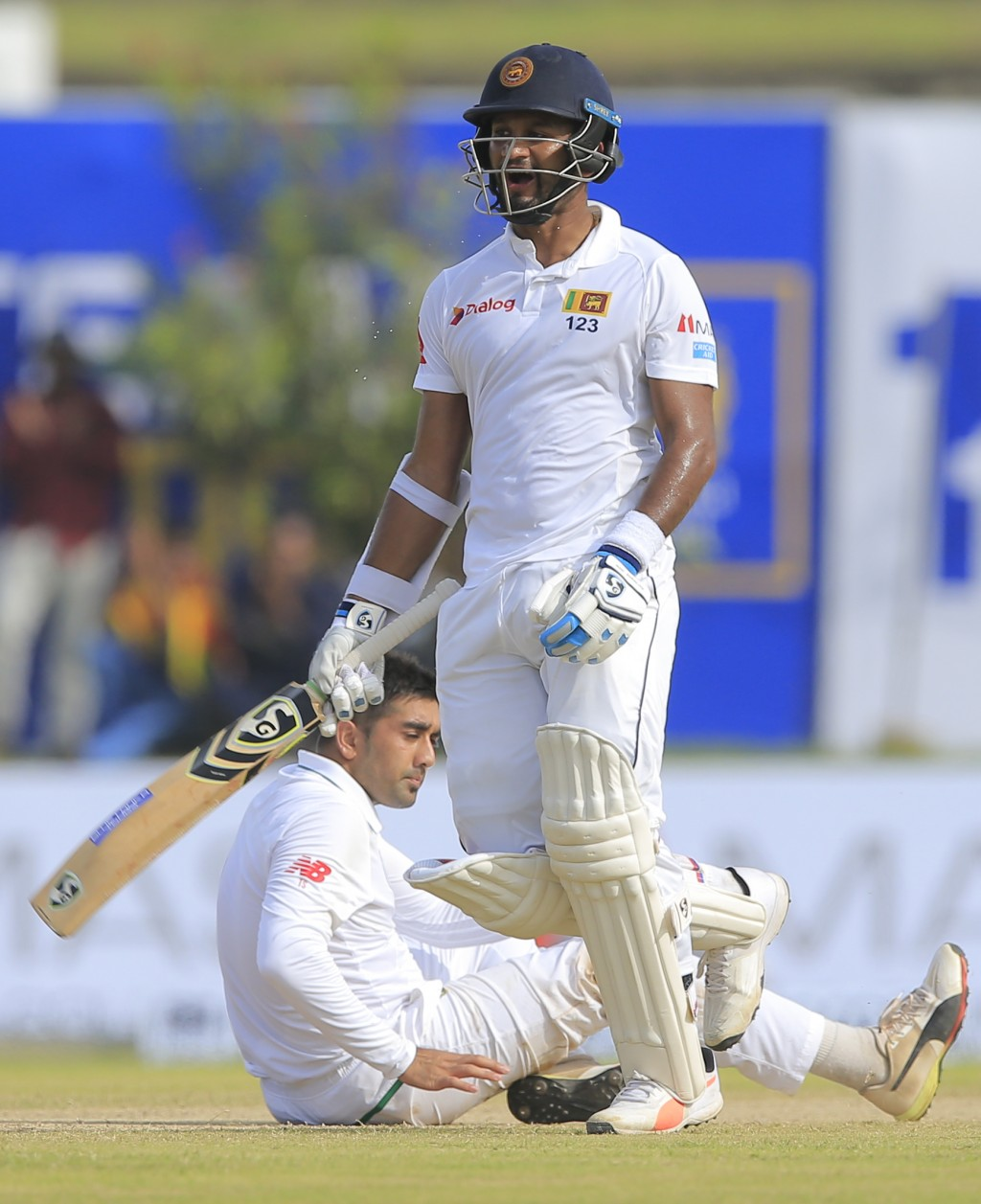 Sri Lanka's Dimuth Karunaratne, right, celebrates scoring hundred runs as Tabraiz Shamsi watches during the first day's play of their first test crick