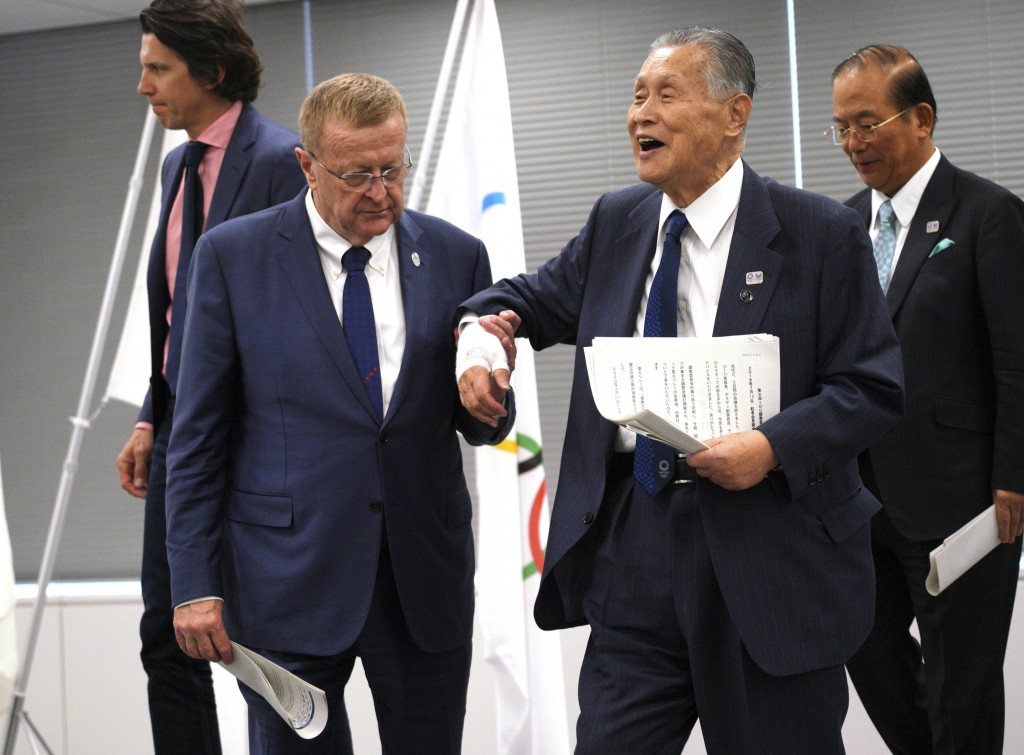 John Coates, left, chairman of the IOC Coordination Commission for the 2020 Tokyo Olympics and Paralympics, helps Tokyo Olympic organizing committee P