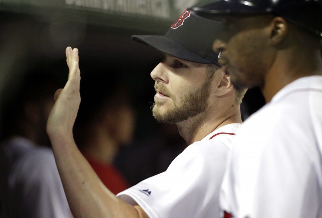 Boston Red Sox's Chris Sale is welcomed to the dugout after pitching in the seventh inning of a baseball game against the Texas Rangers, Wednesday, Ju
