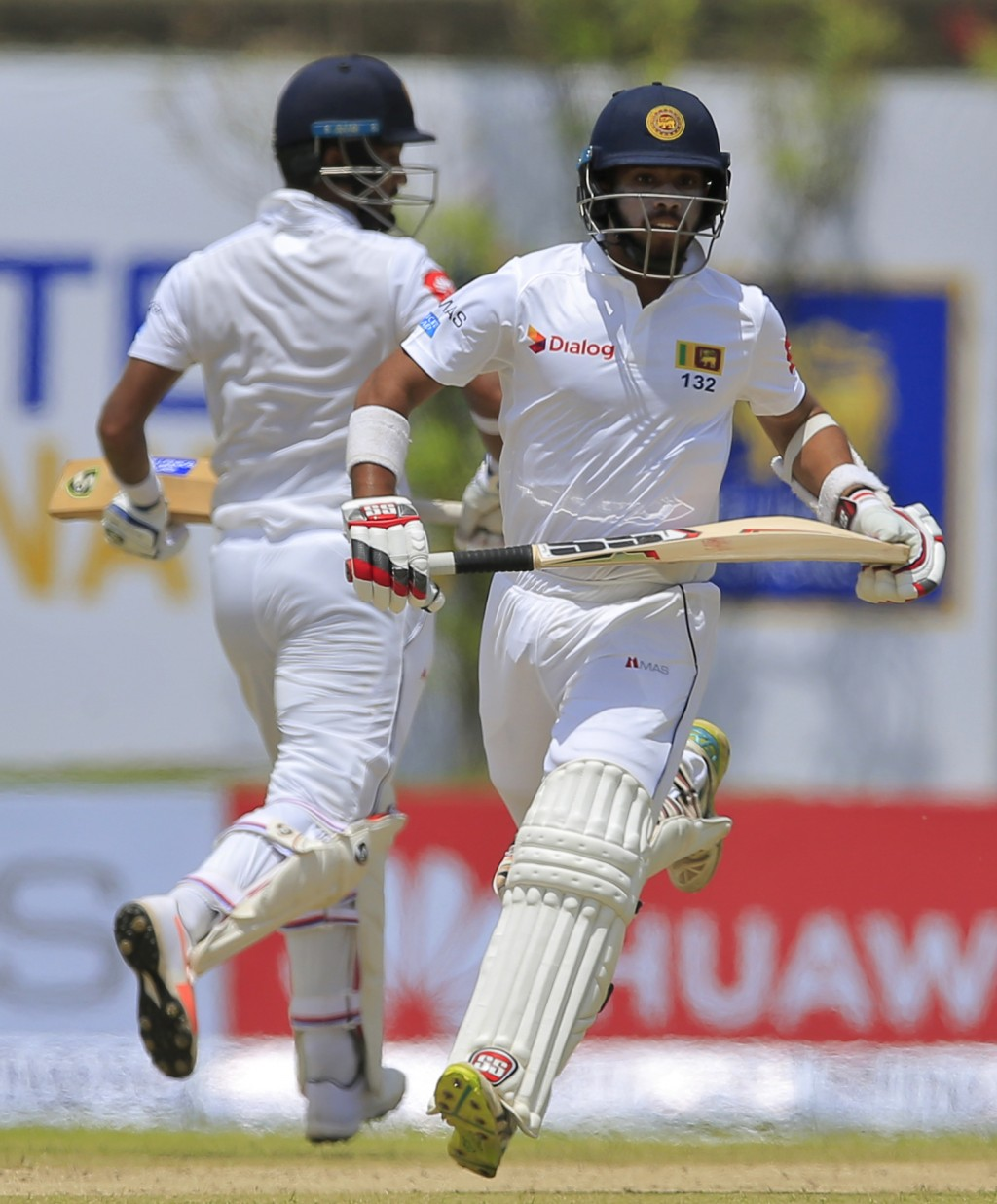 Sri Lanka's Dimuth Karunaratne, left, and Kusal Mendis run between wickets against South Africa during the first day's play of their first test cricke