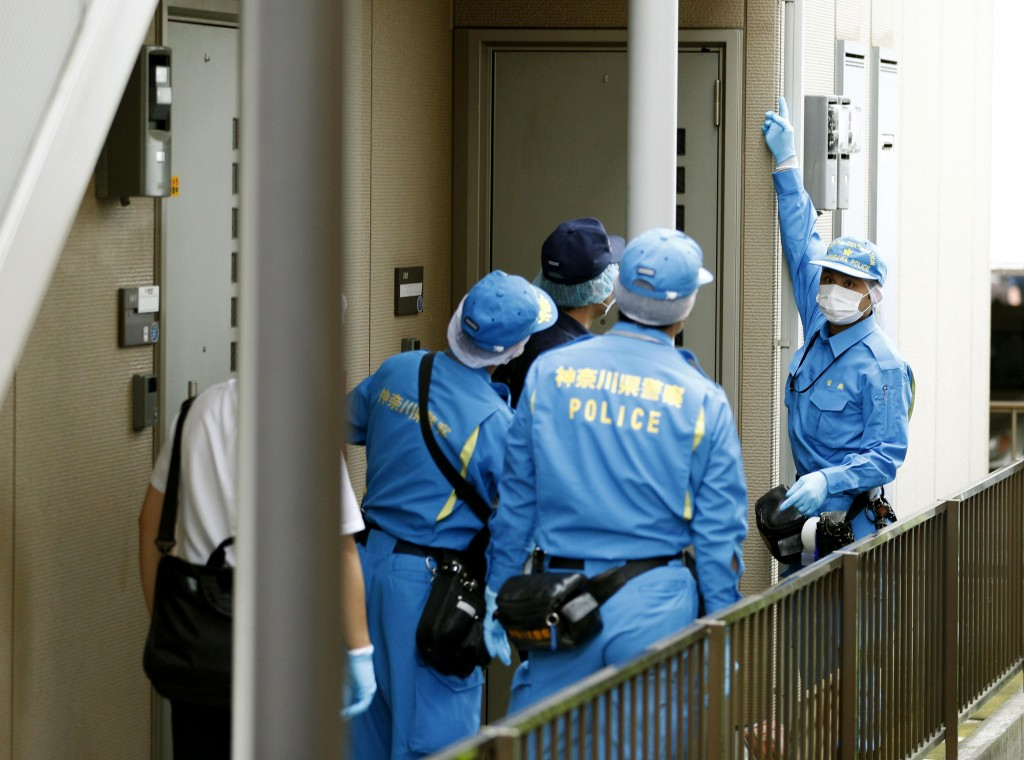 Police investigators head to the house of suspect Ayumi Kuboki in Yokohama. Japanese authorities raided Thursday, July 12, 2018, the apartment of the