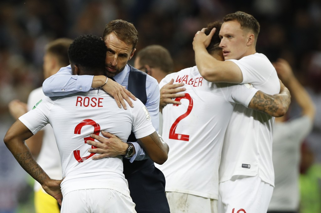 England head coach Gareth Southgate, 2nd left, comforts England's Danny Rose, left, after loosing the semifinal match between Croatia and England at t