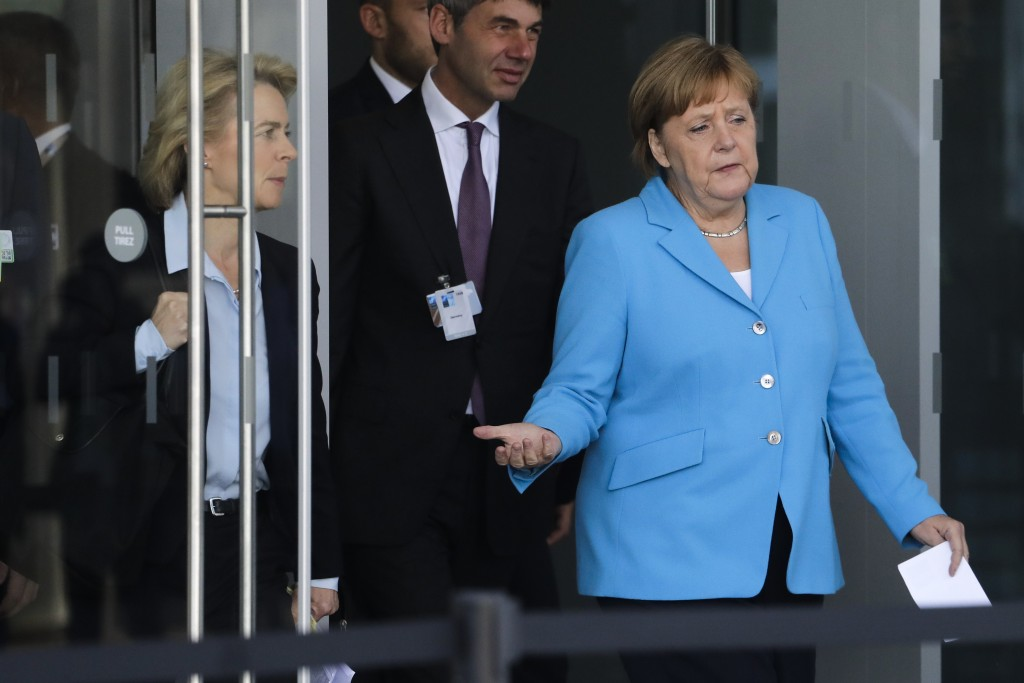 German Chancellor Angela Merkel, right, arrives for a statement with Defense Minister Ursula von der Leyen, left, after a summit of heads of state and
