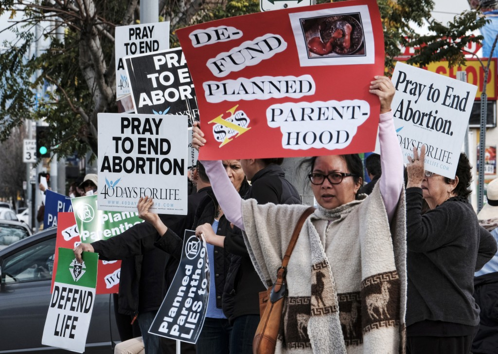 FILE - In this Feb. 11, 2017, file photo, protesters carry signs outside a Planned Parenthood health center in the Van Nuys section of Los Angeles. If