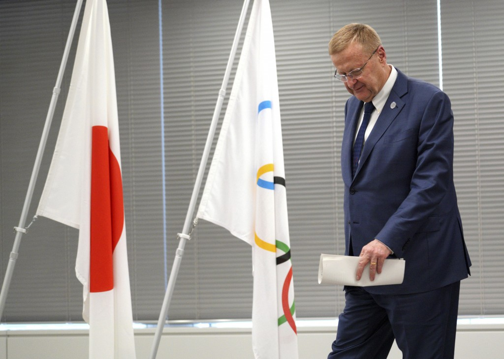 John Coates, chairman of the IOC Coordination Commission for the 2020 Tokyo Olympics and Paralympics walks near a Japanese and the Olympics flags afte