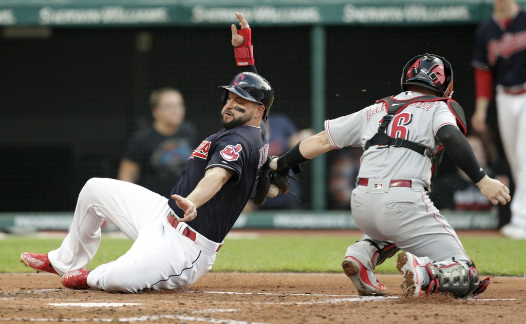 Cleveland Indians' Yonder Alonso, left, slides safely into home plate as Cincinnati Reds catcher Tucker Barnhart can't make the tag during the third i