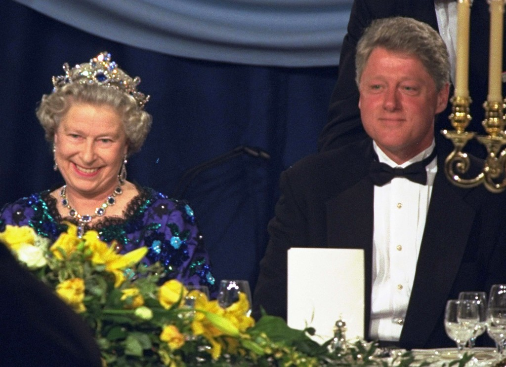 FILE - In this Saturday, June 4, 1994 file photo, Britain's Queen Elizabeth smiles, as she sits alongside President Bill Clinton at a dinner in the Gu